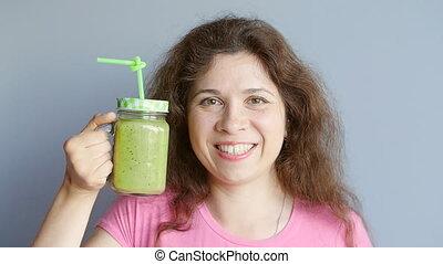Happy woman enjoying vegetable smoothie - Young beautiful...
