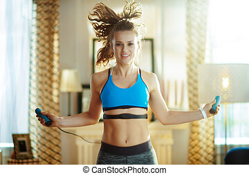 happy woman exercise using jump rope with heart rate monitor