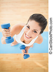 Happy woman exercising with dumbbells on blue exercise mat smiling at camera at home on wooden floor