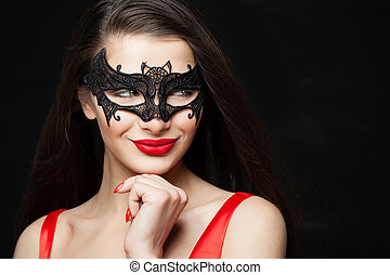 Happy woman fashion model in black mask smiling on abstract night glitter bokeh background