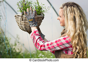 Happy woman fixing a hanging flower basket