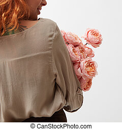 florist at work with pink ranunkulus bouquet on a white background