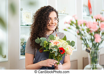 Happy woman florist working in flower shop