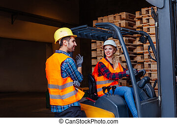 Happy woman forklift driver smiling, looking at the camera