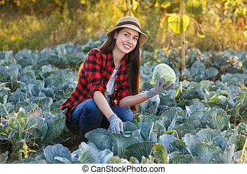 Happy woman gardener with cabbage