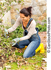 Happy woman gardening bush backyard hobby kneeling - Happy...