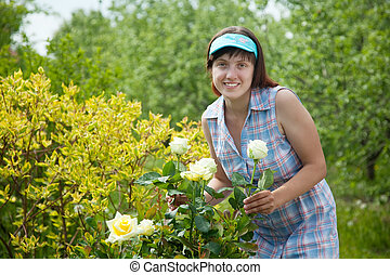 Happy  woman gardening with roses