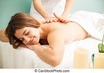 Happy woman getting a massage at the spa