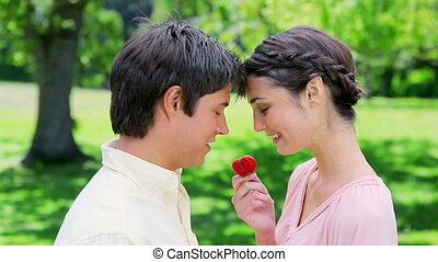 Happy woman giving a strawberry to her boyfriend