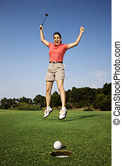 Happy woman golfing. - Caucasion mid-adult woman holding...