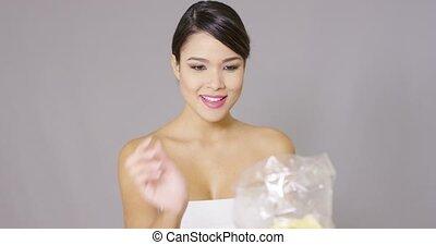 Happy woman grabbing potato crisps - Happy woman grabbing...