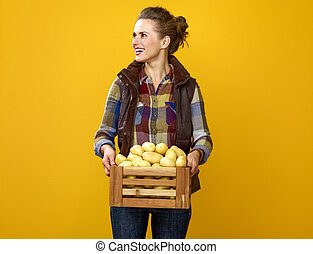 happy woman grower with box of potatoes looking at copy space