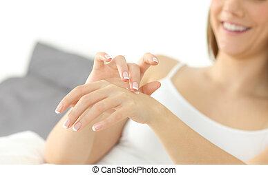 Happy woman hands applying moisturizer cream