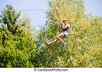 Happy Woman Hanging On Zip Line In Forest - Full length of...