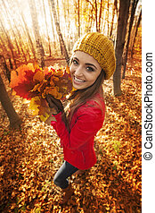Happy woman have fun with leaves during the autumn