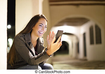 Happy woman having a video call in the night in the street