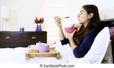 Happy woman having breakfast in bed