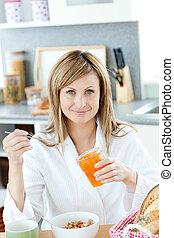 Happy woman having breakfast in the