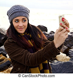 Happy woman having fun taking picture of herself