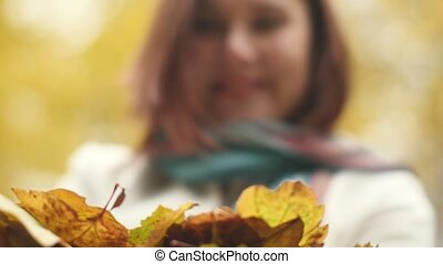 Happy woman having fun throwing leaves in Autumn in slow motion, smiling.