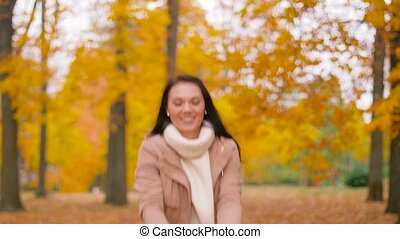 happy woman having fun with leaves in autumn park