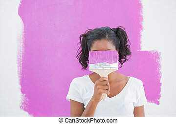 Happy woman hiding her face with paintbrush