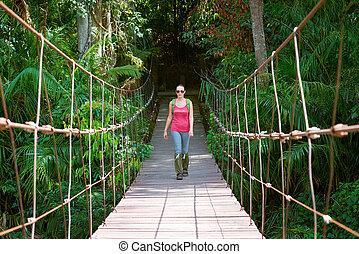 Happy woman hiker crossing suspension bridge in sunlight.