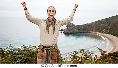 happy woman hiker rejoicing in front of ocean view landscape
