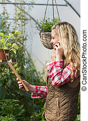 Happy woman holding a clipboard in her green house on the phone