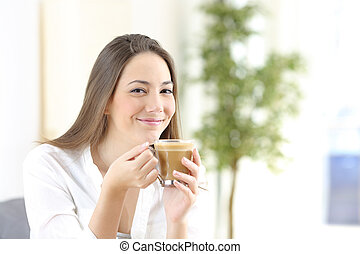 Happy woman holding a coffee cup looking camera