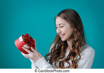 Happy woman holding a gift in the form of heart