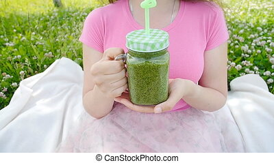 Happy woman holding a green smoothie