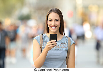 Happy woman holding a phone looking at camera