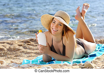 Happy woman holding a sunscreen bottle lotion on the beach