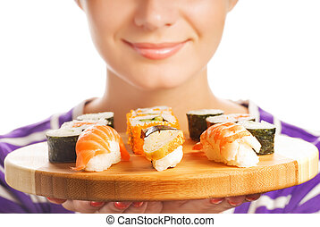 Happy woman holding bamboo plate with fresh sushi set on it (Shallow DoF, focus on sushi)