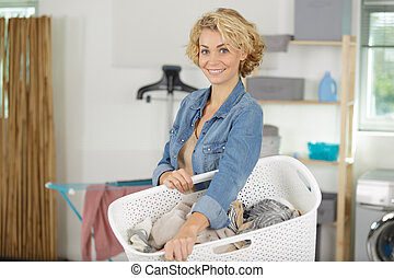happy woman holding basket of clothes in laundry room