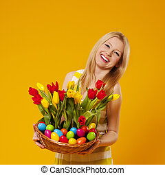 Happy woman holding basket with spring flower and easter...
