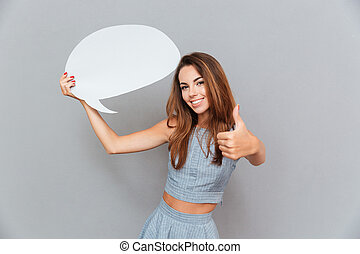 Happy woman holding blank speech bubble and showing thumbs...