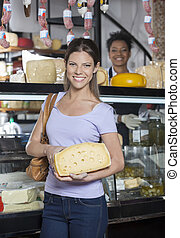 Happy Woman Holding Cheese In Front Of Grocery Shop