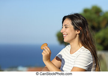 Happy woman holding cookie in a balcony on the beach