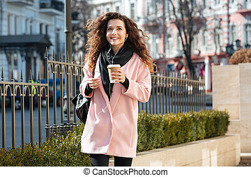 Happy woman holding cup of coffee