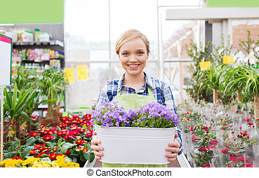 happy woman holding flowers in greenhouse - people,...