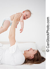 Happy woman holding her baby while lying