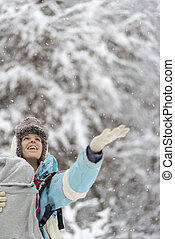 Happy woman holding her hand out to winter snow