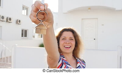 Female hand holding house key. Real estate concept