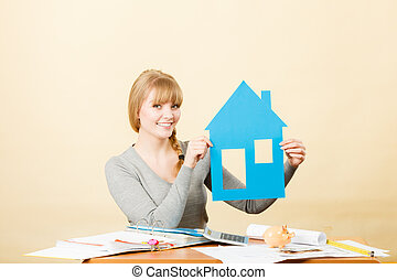 Happy woman holding house model.