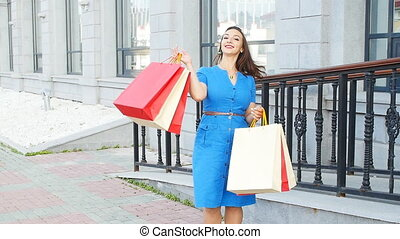 Happy woman holding many shopping bags