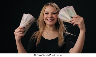 Portrait of happy beautiful woman with blind hand holding in hands money banknotes. Smiling female enjoying rich lifestyle. Black studio background.