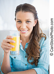 Happy woman holding orange juice