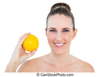 Happy woman holding orange